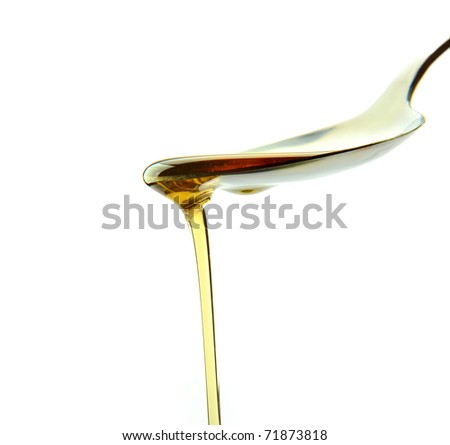 oil poured from a spoon isolated on white - stock photo
