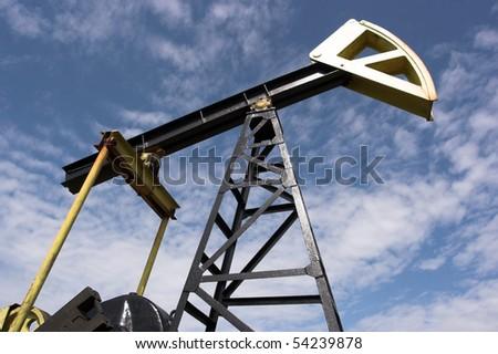 Oil pump jack against blue sky - stock photo