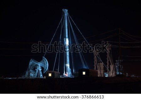 Oil pump jack and drilling rig at the night sky background. Oil fields in Western Siberia. - stock photo