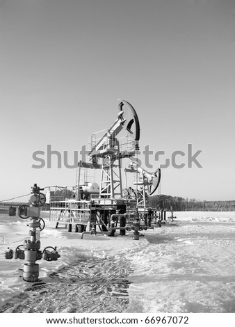 Oil pump jack in work. Oil industry in West Siberia. Siberian frost in sunny day. Black and white - stock photo