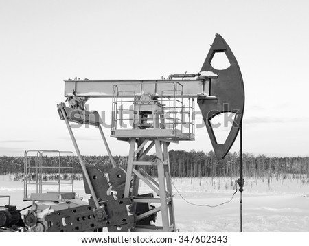 Oil pump jack. Oil industry in West Siberia. Winter frost. Black and white photo - stock photo