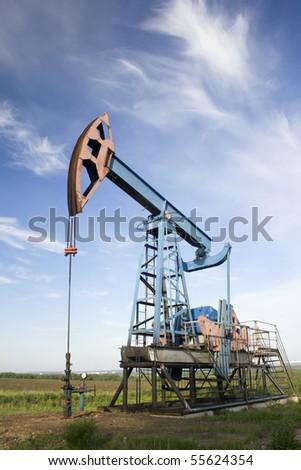 Oil pump jack on a green field - stock photo