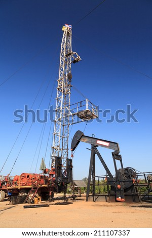 Oil Pump Jack (Sucker Rod Beam) and Workover Rig Working on Oil Well on Sunny Day - stock photo