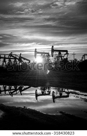Oil pump jacks at sunset sky background. Black and white. - stock photo