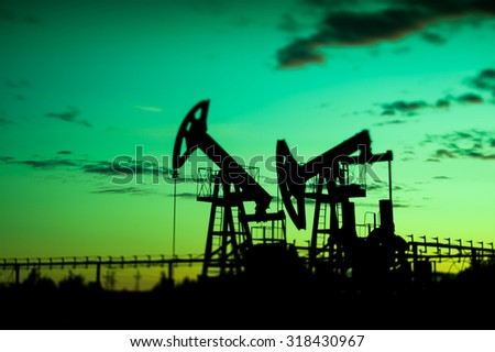 Oil pump jacks at sunset sky background. Selective focus, shallow depth of field. - stock photo