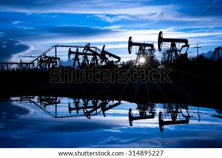 Oil pump jacks group on a sunset sky background. Toned blue. - stock photo