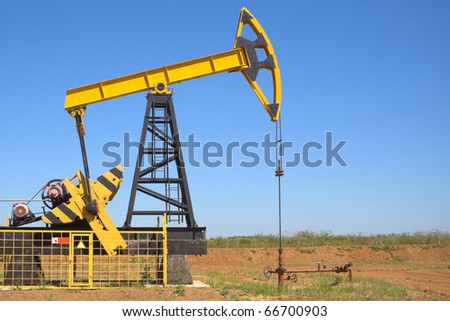 oil pump jacks working at dawn. A pump jack on the plains - stock photo