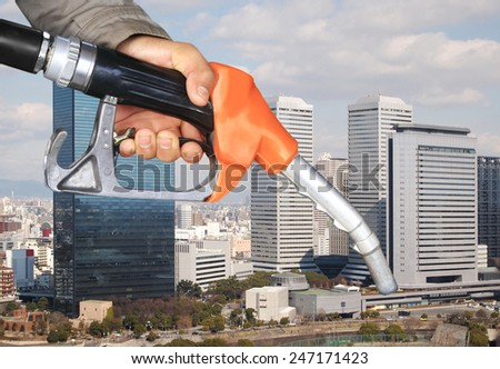 oil pump nozzle and high building city view  - stock photo