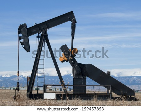 Oil pumpjack against snowy mountains in Colorado. - stock photo