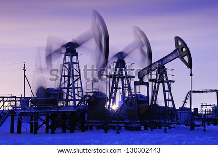 oil pumps at sunset sky background. blue toned. - stock photo