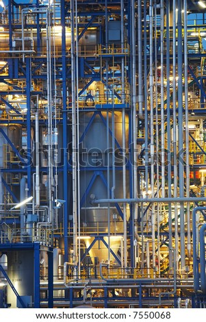 Oil refinery and Distillation Tower surrounded with steaming fumes - stock photo