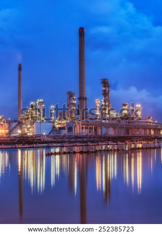 Oil refinery at twilight - petrochemical industry with water reflect. - stock photo