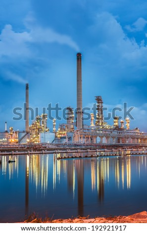 Oil refinery at twilight sky and reflexsion - stock photo