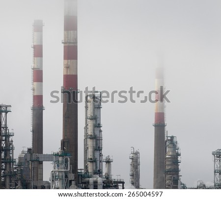 Oil refinery chimneys and towers between fog - stock photo