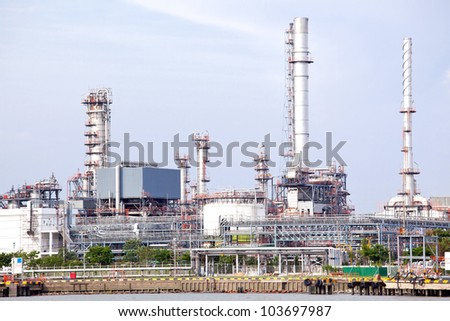Oil refinery plant along river - stock photo