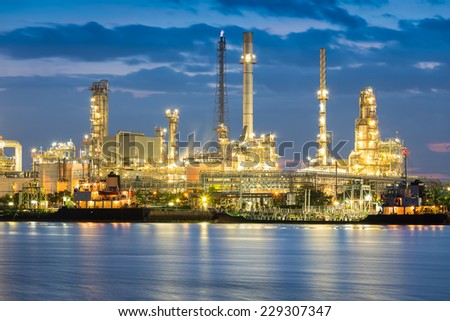 Oil refinery reflected on river at twilight. - stock photo