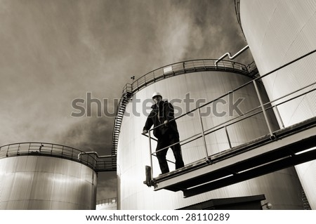 oil refinery tanks in a brown duplex toning, engineer standing on platform - stock photo