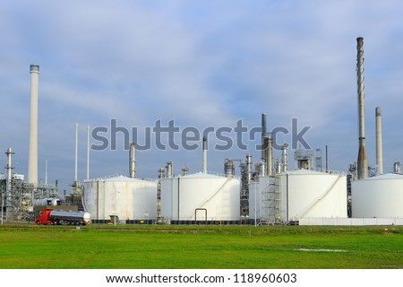 oil refinery with fuel tanker passing by - stock photo