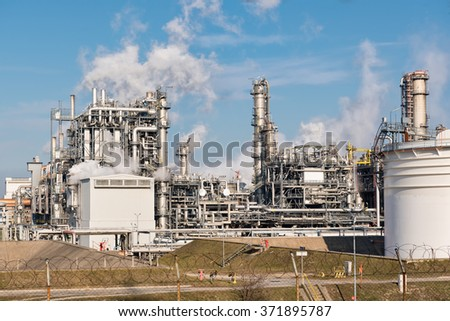 oil refinery with smoking chimneys against blue sky - stock photo