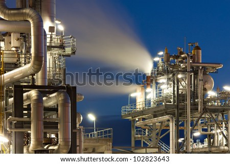 Oil refinery with water vapor in Hamburg, Germany, petrochemical industry night scene - stock photo