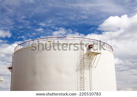 Oil reservoir and blue sky with clouds. Oil industry and gas refinery plant. Industrial scene of oil field  - stock photo