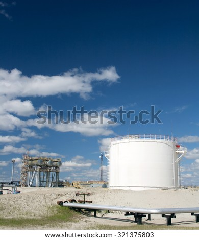 Oil reservoir. Oil and gas refinery plant. Industrial scene of oil field. Blue sky with clouds above gas station - stock photo