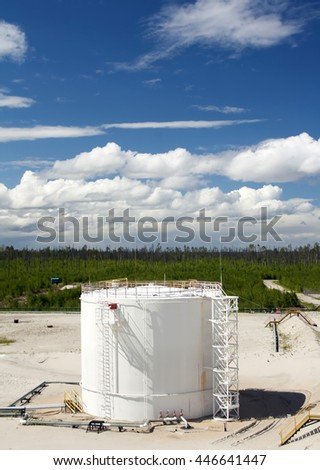 Oil reservoir. Oil and gas refinery plant. Industrial scene of oil field. Blue sky with clouds above gas station. - stock photo