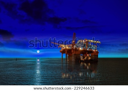 Oil Rig at night time and the moon. - stock photo