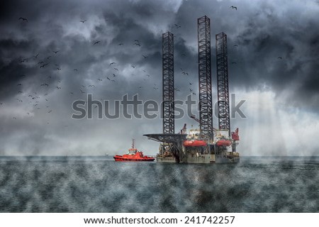 Oil Rig at sea on a dark cloudy dramatic sky. - stock photo