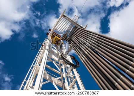 Oil rig derrick in oilfield against the bright blue sky - stock photo