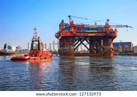 Oil rig in the company of a tug boats enters a port. - stock photo