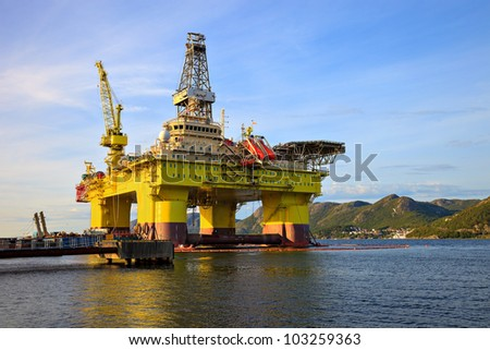 Oil rig near the mountains in Norway. - stock photo