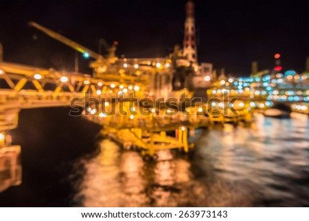 oil rig platform in the night take by out focus - stock photo