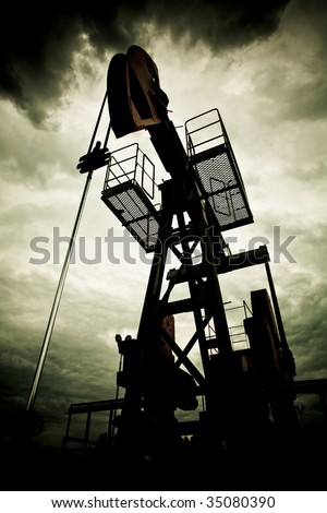 Oil rig pump dramaticly underexposed against contrast cloudy sky - stock photo