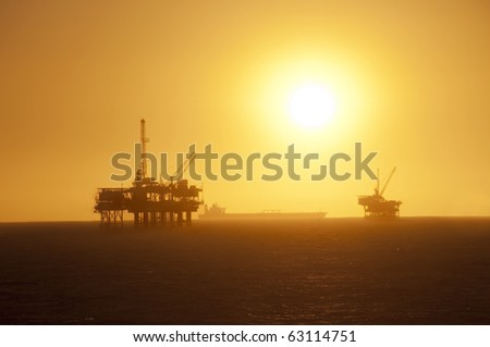 Oil Rigs in the ocean, ship passing by and a beautiful sunset in Huntington Beach, California. - stock photo