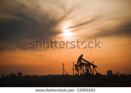 Oil rigs silhouette over orange sky-2 - stock photo