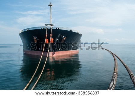 Oil tanker is transferring supply to the cargo vessel - stock photo