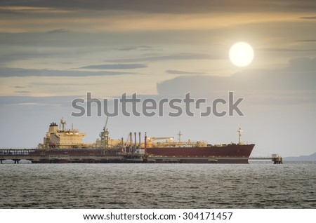 Oil Tanker loading oil in the sea at sunset - stock photo