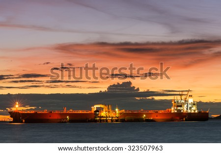 Oil Tanker loading oil in the sea with sunset - stock photo