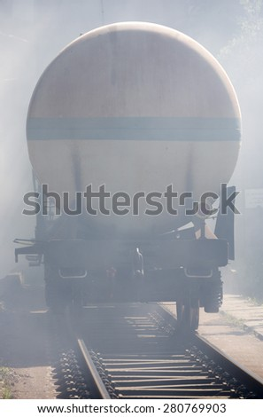 Oil tanker train is seen in smoke near Sofia. Fire safety and civil protection service at Fire department is training in a situation of train crash with flammable materials from the cargo tanks. - stock photo