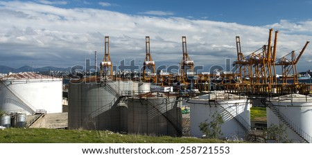 Oil tanks in the port with loading cranes and tankers on the background - stock photo