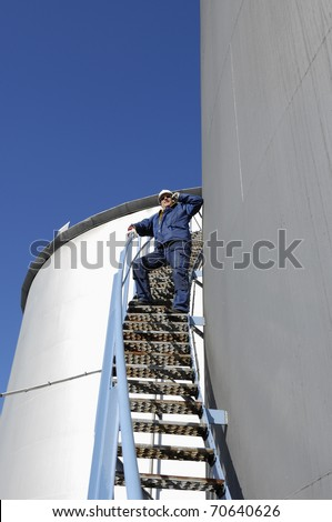 oil worker and giant industrial fuel storage tanks, as seen inside oil refinery - stock photo