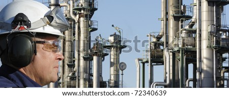 oil-worker, engineer, in close-ups, with large oil refinery industry in background - stock photo