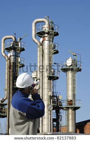 oil-worker, engineer, pointing at oil and gas towers - stock photo