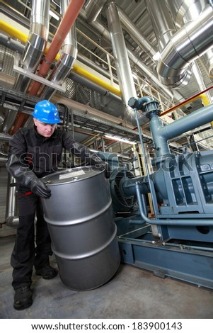 Oil Worker in coveralls,hardhat and rubber gloves dealing with silver oil barrel - stock photo