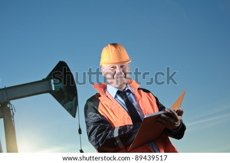 Oil worker in orange uniform and helmet on of background the pump jack and blue sky. - stock photo