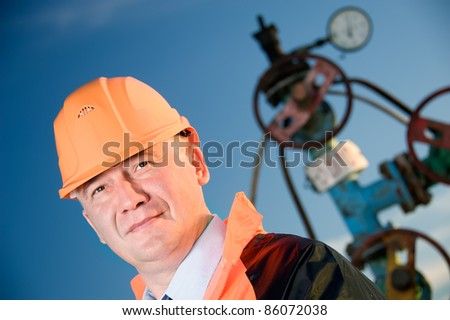 Oil worker in orange uniform and helmet on of background the valves, piping and sunset sky. - stock photo