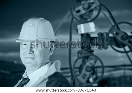 Oil worker in uniform and helmet on a background the valves, piping and sunset sky. Toned. - stock photo