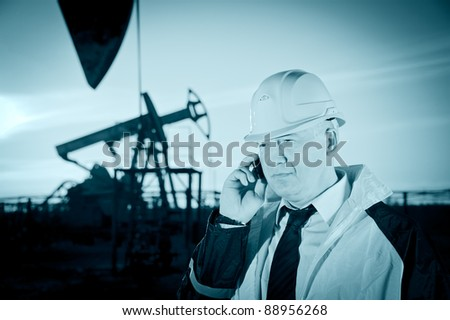 Oil worker in uniform and helmet, with mobile phone on of background the pump jack and sky. Toned. - stock photo
