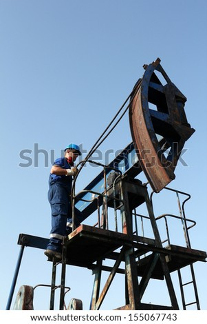 oil worker on pump jack - stock photo